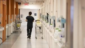 Un homme marche dans le couloir d'un hôpital.