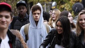 Un adolescent vête d'un chandail à capuchon marche au milieu d'autres adolescents.
