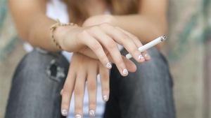Une adolescente tient une cigarette entre ses doigts.