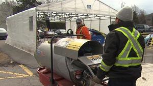 Des hommes portant du matériel près d'une tente en construction.