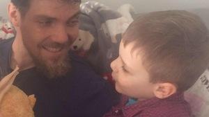 Un papa et son garçon se regardent et se sourient.