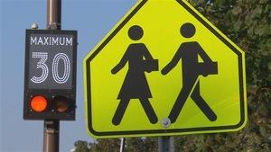 Deux panneaux, un illuminé montrant la vitesse permise et l'autre jaune arborant deux enfants qui marchent.