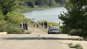 Des agents et des voitures de police près d'un cours d'eau