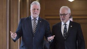 Carlos Leitao et Philippe Couillard marchant dans un corridor de l'Assemblée nationale.