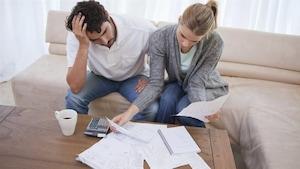 Un couple dans son salon se penche sur des papiers.