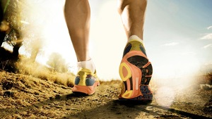 Un homme court en sentier chaussé d'espadrilles jaune, orange et noir.