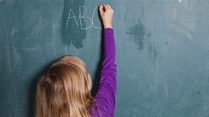 Enfant écrivant les lettres ABC à la craie sur un tableau noir