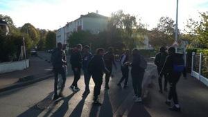Des jeunes français marchent dans une rue résidentielle.