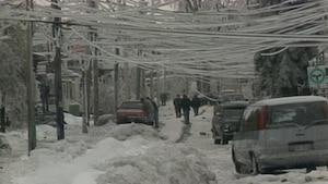Des files électriques couverts de glace pendent dangereusement à quelques mètres au dessus de la rue à Montréal.