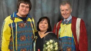 Deux hommes entourent une femme qui tient des fleurs.