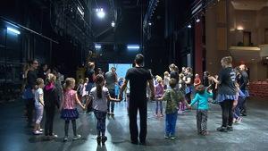 Des enfants en cercle sur une scène