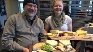 Un homme et une femme présente des plateaux de fromage.
