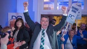 Dennis King lève les deux bras dans les airs, poings fermés, pour célébrer sa victoire. Autour de lui, des militants de son parti se réjouissent et tiennent des pancartes.