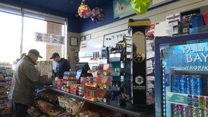 Un client paye au comptoir d'un dépanneur