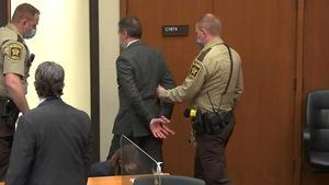 Derek Chauvin est escorté par deux policiers.
