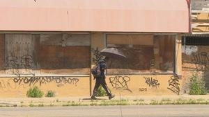 un homme marche avec un parapluie noir devant un mur de graffitis