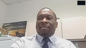 Un homme de couleur noire portant une cravate dans un bureau.