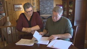 Donda et David Holt feuillettent les papiers envoyés par le ministère du Développement social.