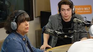 Une femme d'âge mûr assise à la gauche d'une table et un jeune homme assis à droite