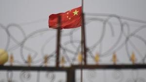 Des barbelés devant un drapeau de la Chine.