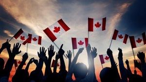 Une foule agite dans les airs des drapeaux canadiens.