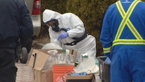 Un policier en uniforme hazmat se penche sur un ramassis de matériel de laboratoire sur le bord de la rue