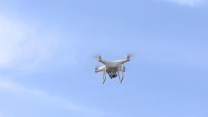 Un drone blanc dans les airs, sur fond de ciel bleu