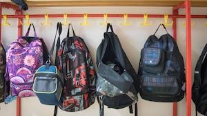 Des sacs à dos d'élèves accrochés sur un mur.