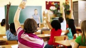Des élèves sont assis en classe et lèvent le bras pour prendre la parole. Ils sont de dos.