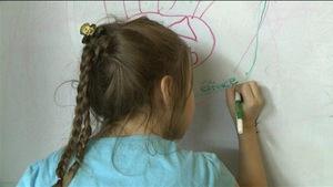 Une écolière écrit au tableau.