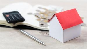 Une maison miniature repose près d'une calculatrice, un stylo et des pièces de monnaie.