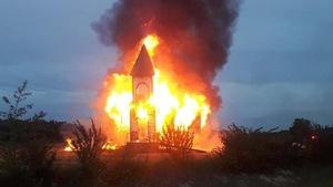 Une église complètement en feu, un énorme nuage de fumée épaisse est au dessus de celle-ci.