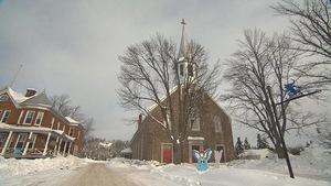 Église de Saint-Élie-de-Caxton en hiver avec un lutin sur un poteau