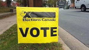 Le mot « VOTE » en grosses lettres sur une affiche jaune d'Élections Canada plantée dans le gazon.