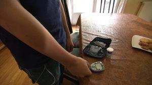 Un garçon utilise un glucomètre.