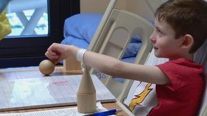 un petit garçon alité joue avec des objets sur un bureau comme à l'école
