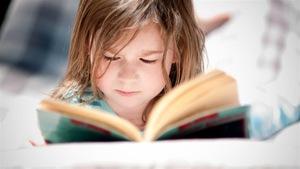 Un enfant allongé lit un livre.