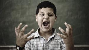 Un enfant debout devant un tableau d'école, la bouche grande ouverte pour crier et les yeux plissés de rage lève les mains, paumes vers le ciel.