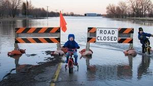 Des enfants à vélo dans une rue inondée