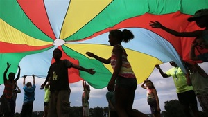 Des enfants jouent sous un grand chapiteau de tissu coloré.
