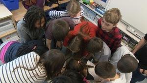 Les enfants, massés en cercle, se consultent.