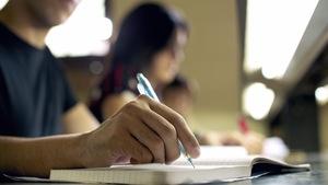 Un élève prend des notes dans une salle de classe.