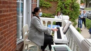 Une dame joue du piano sur son balcon devant une foule de passants.