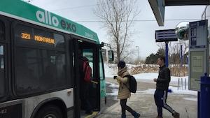 Des personnes montent à bord d'un autobus.