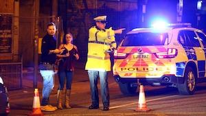 Un policier britannique indique le chemin à suivre à des passants après l'explosion.
