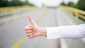Un individu fait du pouce sur le bord d'une route