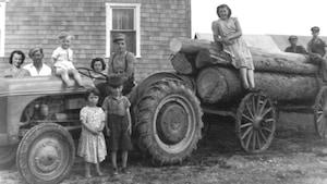 Une photo d'époque de la famille Blais de Hearst en 1950 sur laquelle on retrouve les parents et 8 enfants rassemblés autour d'un tracteur et des billots de bois sur une remorque.
