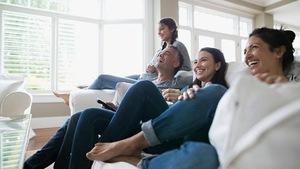 Une famille assise dans un divan rit en regardant la télévision.