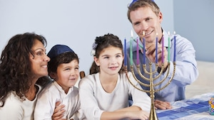 Des parents et leurs deux enfants sont attablés. Le père allume les chandelles d'une menora.