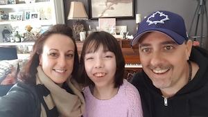 Les trois personnes prennent une photo dans le salon familial